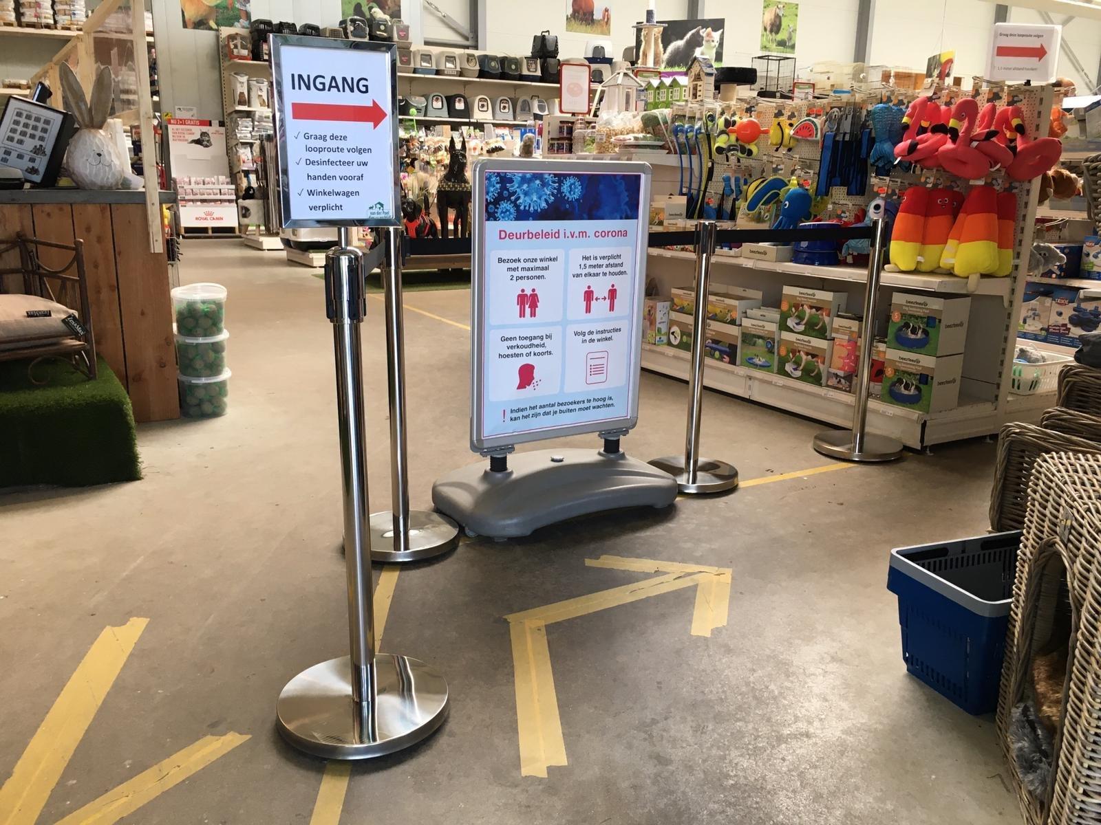 Afzetpaaltjes met lint voor winkels om afstand te houden bij Covid19